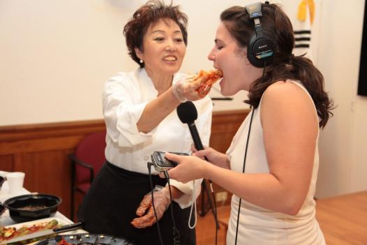 Chef Young Lee offers Reporter Emily Friedman a taste of cabbage kimchi.