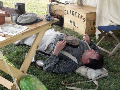 A Civil War reenactor basks in the shade for a little relief from the heat at the Manassas battlefield.