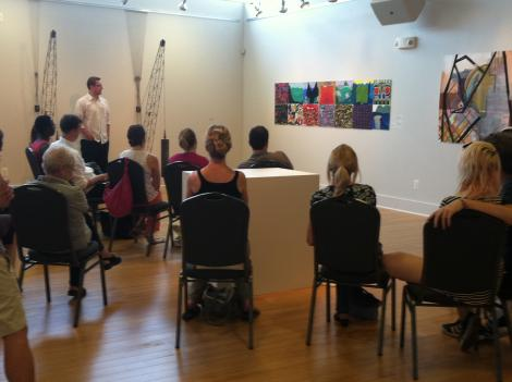 "Brett John Johnson (standing, left) leads a public discussion of the ""D.C. Emerging"" art show at VisArts gallery in Rockville, Md. Crane sculptures on the left are by Sean Lundgren. Paintings in the center are by Mike Dowley, and the painting on the right is by Mariah Ann Johnson. All five artists in the show live in the D.C. area."