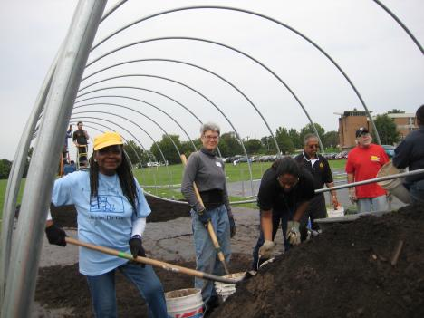 "Volunteers at Lake Clifton High School work to build a ""hoop house,"" where farmers will grow vegetables for Baltimore City schools."