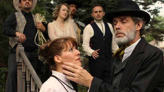 """Judge Roy Bean (Scott Sedar), also known as """"the Pasha,"""" intimidates the captive Lillie (Heather Bingham) before a group of onlookers in The In Series' production of Mozart's Abduction from the Seraglio."""