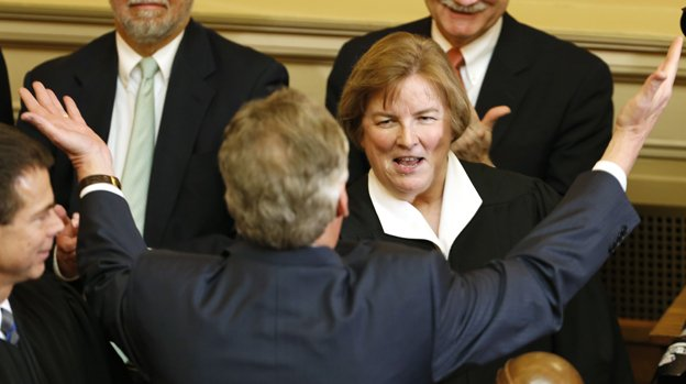 Virginia Gov. Terry McAuliffe, back to camera, reaches to hug Virginia Supreme Court Justice, Jane Marum Roush, as he arrives to deliver his State of the Commonwealth Address before a joint session of the 2016 Virginia Assembly at the Capitol in Richmond, Va., Wednesday, Jan. 13, 2016.