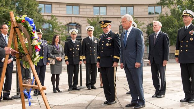 Defense Secretary Chuck Hagel, center right, and Joint Chiefs Chairman Gen. Martin Dempsey, center left, lead a delegation at the Navy Memorial in Washington to remember the victims of Monday's deadly shooting at the Washington Navy Yard, Tuesday, Sept. 17, 2013. At far right is Chief of Naval Operations Adm. Jonathan Greenert, with Secretary of the Navy Ray Mabus, second from right.