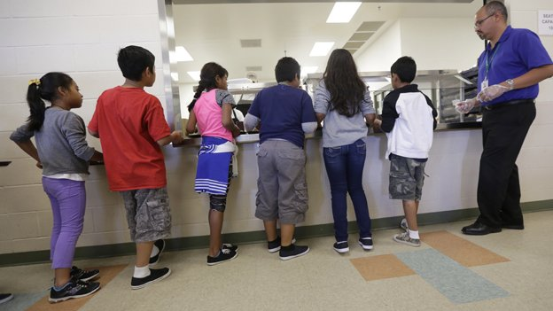 Detained immigrant children line up in the cafeteria at the  Karnes  County Residential Center,  a temporary home in Texas for immigrant women and  children detained at the border. Many of the unaccompanied children from such facilities have been relocated to the D.C. region.