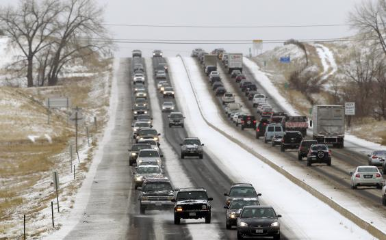 Traffic winds its way east and west along a snowy Boulder-Denver Turnpike, in Superior, Colo., Wednesday. A storm that has dumped more than a foot of snow in the Rocky Mountains is heading east and is forecast to bring the first major winter storm of the season.
