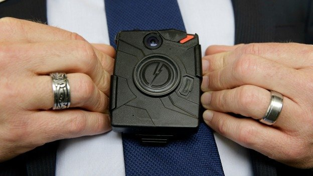 In this Feb. 19, 2015 file photo, Steve Tuttle, vice president of communications for Taser International, demonstrates one of the company's body cameras for The Associated Press during a company-sponsored conference hosted by Taser at the California Highway Patrol Headquarters in Sacramento, Calif.