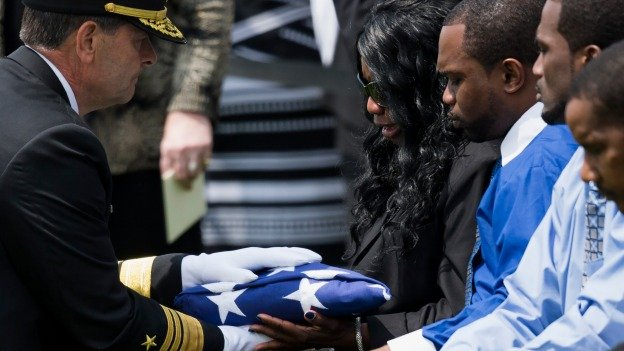Vice Adm. William F. Moran, left, presents a flag to Sharon Blair, mother of U.S. Navy Petty Officer 2nd Class Mark Mayo, of Hagerstown, Md., during a burial service at Arlington National Cemetery in Arlington, Va., Friday, April 25, 2014.