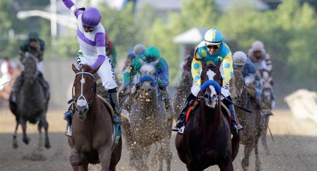 Jockey Mario Gutierrez, left, aboard, I'll Have Another, reacts after crossing the finish line in front of Bodemeister, right, ridden by Mike Smith, to win the 137th Preakness Stakes horse race at Pimlico Race Course, Saturday in Baltimore.