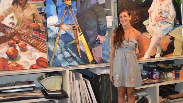 Artist Nicole Bourgea poses in front of some of the life size portraits she painted of random people in the city.