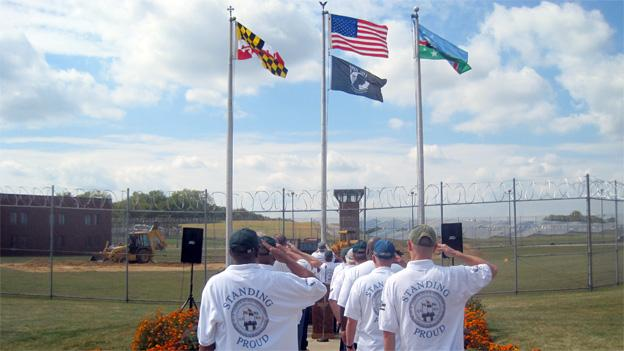 The vets at Roxbury Correctional Institute salute the flag at the memorial.