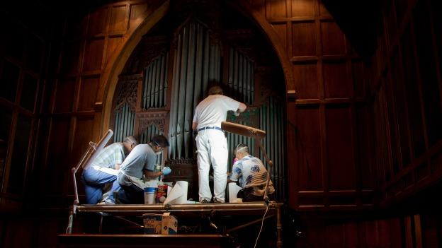 William Adair of Gold Leaf Studios, third from left, works with his staff to remove green paint from the organ in the Washington National Cathedral's historic Bethlehem Chapel, Tuesday, July 30, 2013, in Washington.