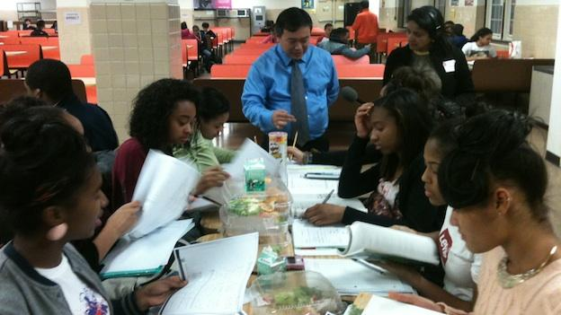 Math Teacher Amadour Jomuada tutors his sophomore geometry students in the cafeteria after school at Benjamin Banneker High School.