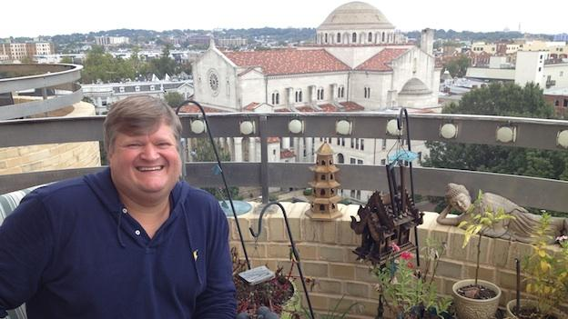 Andrew Hartman enjoys the view from his balcony in Mount Pleasant, D.C.