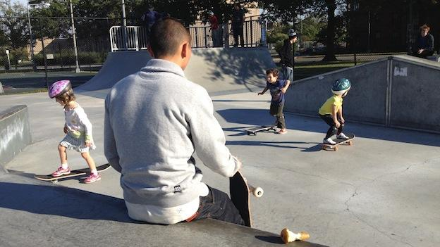 Daniel Kim looks on as his students practice riding and stopping on their skateboards.