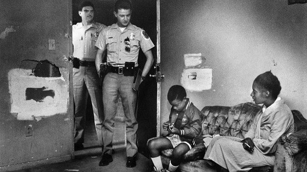P.G. County police officer Alex Bailey (right) and his partner stand in the doorway of the Waters apartment just before Dooney left to go to school at about 7:30 a.m. in Prince George's County, Md. on September 3, 1989.