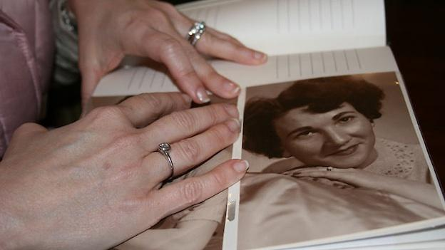 Jeannie Beidler wears her grandmother's ring. This is a photo of her hand wearing the ring as she looks at a photo of her grandmother wearing the same ring.