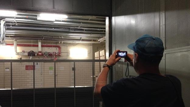 Andrew Reams taking photos of an elevator.