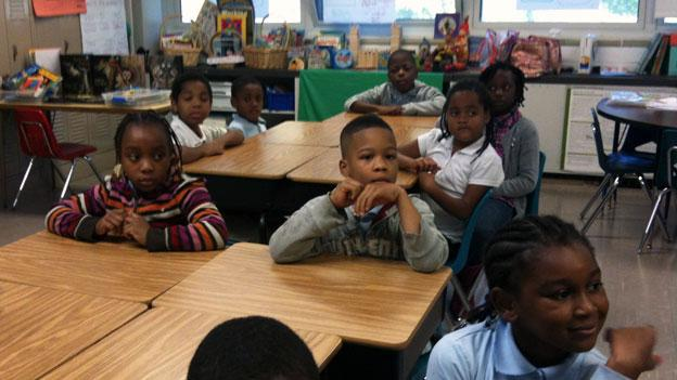 Students listen intently to teacher Glenness Pujoue in their third grade class. At their school, Turner at Green Elementary, just 45 percent of students read and do math at their grade levels.
