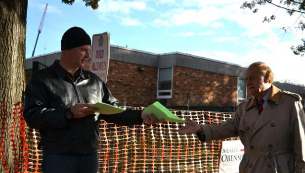 Poll worker Heath Wells hands out Republican sample ballots to Virginia voters.