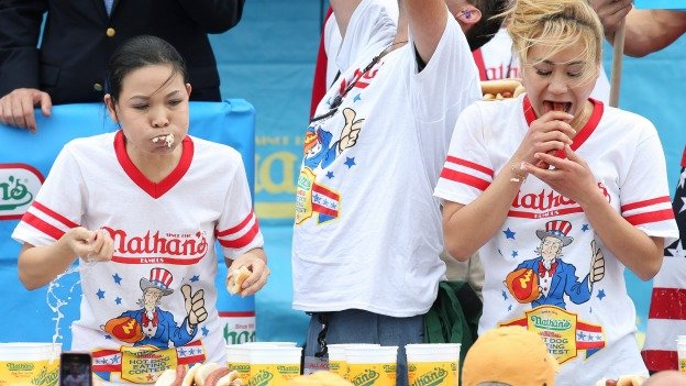 Sonya Thomas, left, and Miki Sudo, right, compete at the Nathan's Famous Fourth of July International Hot Dog Eating contest at Coney Island, Friday, July 4, 2014, in New York. Sudo defeated the reigning champion Thomas by eating 34 hot dogs and buns.