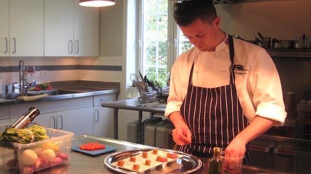 Chef Simon Liestøl Idsøe prepares an amuse bouche containing Norwegian brown cheese and Norwegian salami.