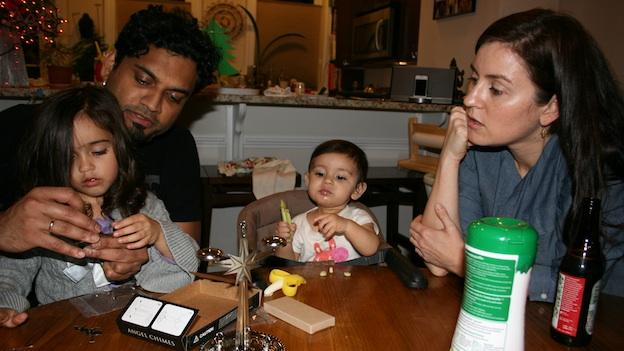 The Mistry family assembles Angel Chimes, a Christmas tradition. Neeraj Mistry holds daughter Nayna, as her sister, Zayne, and her mother, Allison Hodges Mistry, look on.