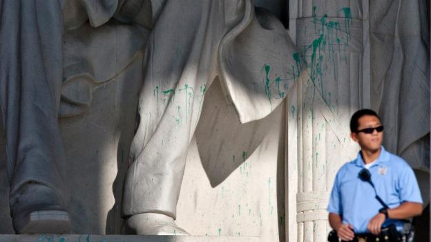 A U.S. Park Police officer stands guard next to the statue of Abraham Lincoln at the memorial after the memorial was closed to visitors after someone splattered green paint on the statue and the floor area.