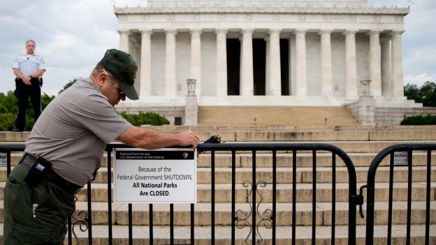 A U.S. Park Police officer watches at left as a National Park Service employee posts a sign on a barricade closing access to the Lincoln Memorial in Washington, Tuesday, Oct. 1, 2013.