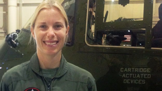Marine Corp. Captain Charlene Thoreen poses in front of a helicopter.