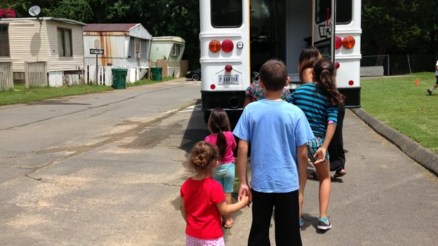 Kids at the Marumsco Mobile Home Park in Woodbridge, Virginia, wait in line for their free lunch from the Kids Food Bus.