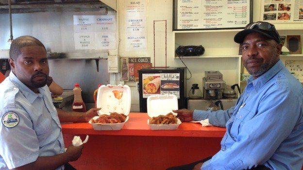 Two customers at Smokey's in Petworth, which they insist has the city's best mumbo sauce.