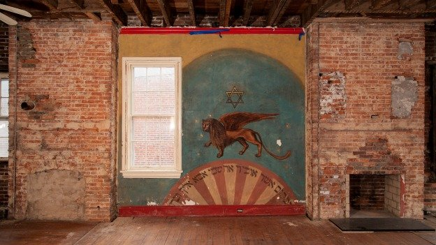 The mural is painted directly onto the plaster walls of 415 M Street, squeezed between a window and a fireplace. When Black Rock Holdings took possession of the building, they avoided removing the mural in their initial demolition, thinking that it held some historical significance.