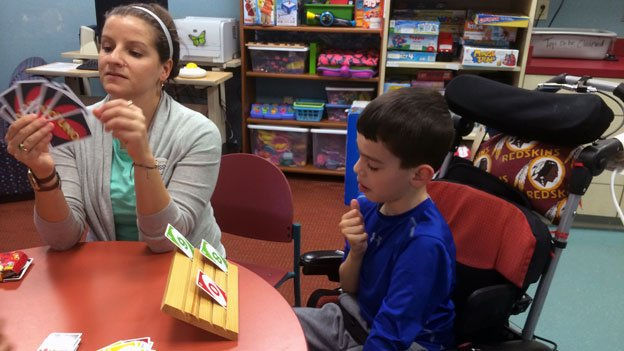 Nico Loza practices speech and movement, playing Uno with speech therapist Missy Licata at MedStar National Rehabilitation Hospital.
