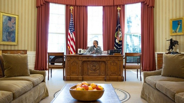 President Barack Obama makes a Thanksgiving Day phone call to a member of the U.S. military stationed overseas, from the Oval Office, Nov. 28, 2013.