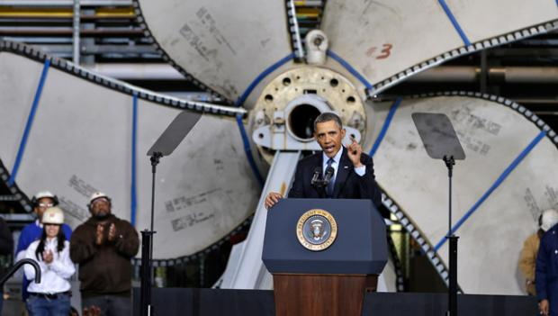 Standing in front of a ships propeller, President Barack Obama, gestures during a speech about automatic defense budget cuts, Tuesday, at Newport News Shipbuilding in Newport News, Va.