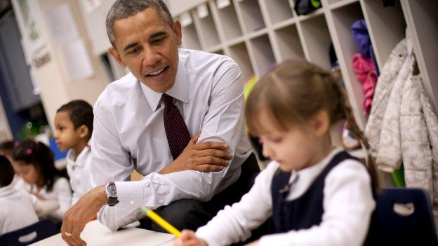 President Barack Obama sits with Emily Hare as she completes her spelling lessons during his visit to a preschool classroom at Powell Elementary School in the Petworth neighborhood.