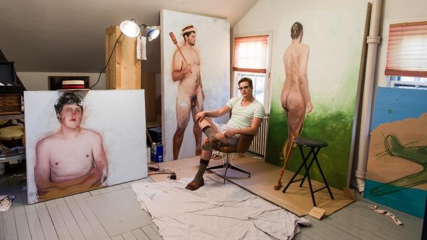 Artist Martin Swift poses with three of the oil paintings featured in his Paradox of Masculinity exhibit.