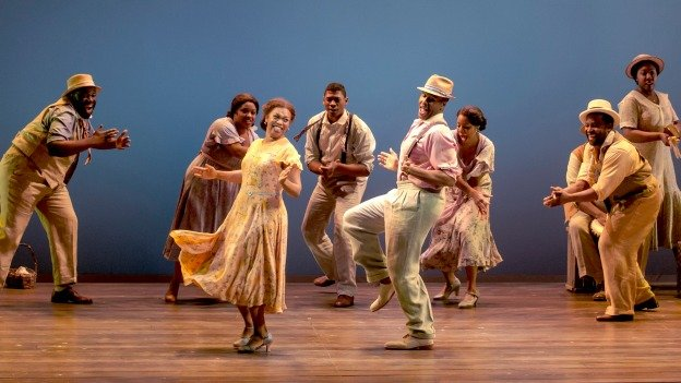 The cast of The Gershwins' Porgy and Bess dance on stage.