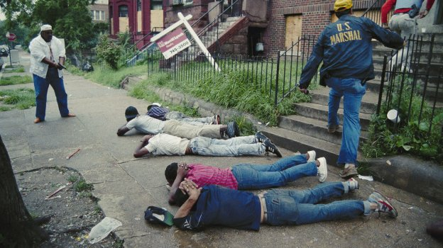 In this photo, released July 17, 1989, a U.S. marshal keeps his pistol trained on suspects as other marshals raid a crack house in Washington, D.C. The city's crack epidemic lasted from the late '80s to the early '90s.