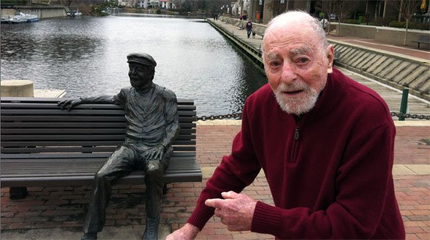 Robert Simon pointing to his likeness on the shore of Lake Anne in Reston, Va.
