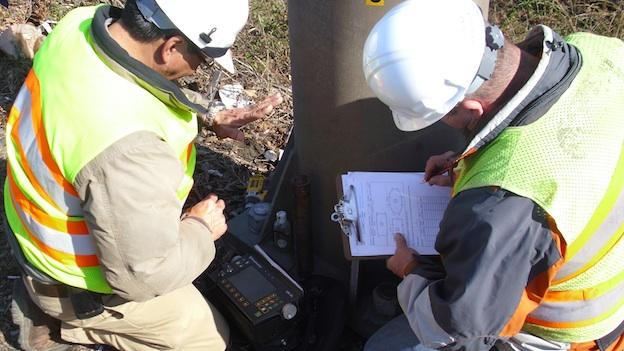Technicians with the Virginia Department of Transportation use an ultrasound machine to test bolts holding down a highway sign.