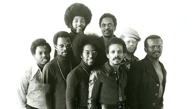A promotional shot of the Soul Searchers from 1974 shows, from left to right: Keni Scoggins, Lino Druitt, Bennie Braxton, John Buchanan, Chuck Brown, John Euell, Lloyd Pinchback, Donald Tillery.