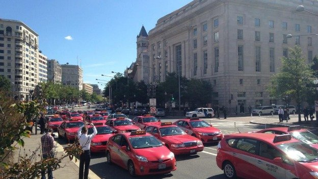 Taxicab drivers are blocking Pennsylvania Avenue in front of the Wilson Building in downtown D.C.