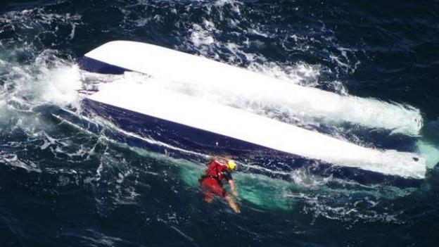 The two men died after their 28-foot catamaran capsized in rough seas on Monday. Two other men survived after being rescued by nearby fishing vessels.
