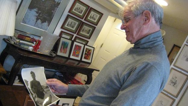 Cliff Brody looks at an old photo of his deceased friend/sergeant, Joe Blakely, who changed Cliff's life during the Vietnam War.
