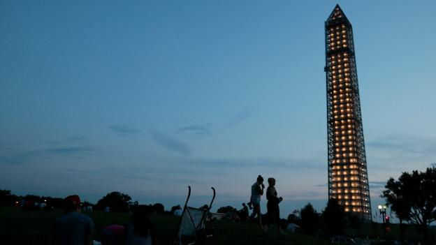 The Washington Monument is lit while undergoing repairs Monday, July 8, 2013 in Washington. The National Park Service will light the monument each night at dusk while it undergoes repairs from the 2011 earthquake. It is expected to reopen in spring of 2014.