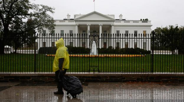 A lone man wearing a rain pouch walks past the White House in Washington, Monday, Oct. 29,2012, during the approach of Hurricane Sandy.