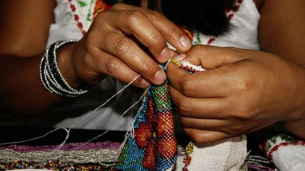 A woman painstakingly sews tiny beads onto a piece of fabric. Beaded bags and clothing appear in the Guerrero 7 exhibit alongside silver jewelry, wooden toys, and colorful masks from the state's different regions.