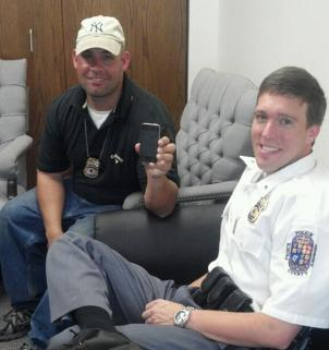 Prince George's County police officers with David Pogue's iPhone after it was recovered.