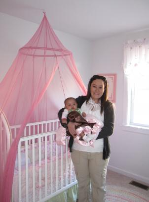 Theresa Holston holds her daughter Layla in the nursery of her new furnished apartment.